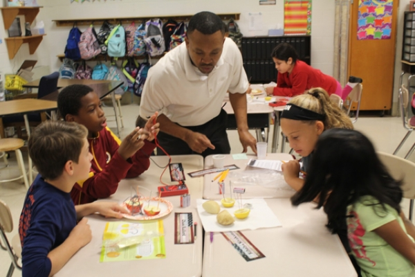 Brian Smith helps 5th Graders at Sherwood Elementary measure the voltage created by batteries made of fruits and vegetables